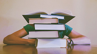 student laying head down behind books